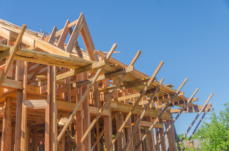 construction frame house made of wood, with roof rafters metal, profiled Imagens