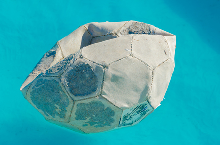 old ragged ball in the water on a Sunny summer day