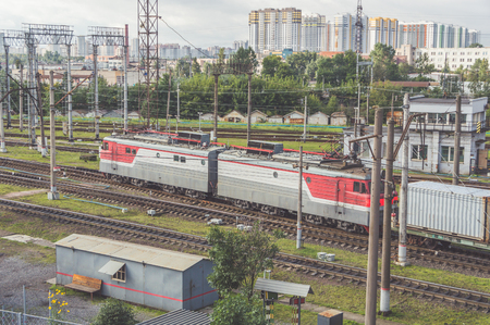 railway locomotive drags freight cars on the background of the city Фото со стока