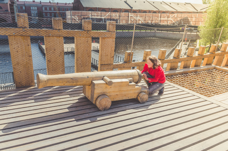 child, girl on a wooden Playground in the form of a pirate ship for artillery gun