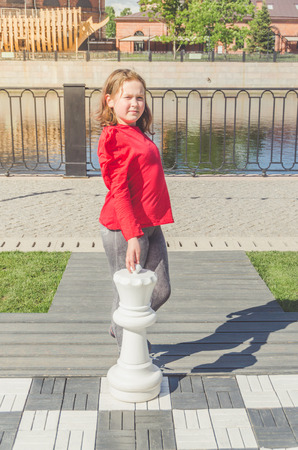 a child, a girl on a large chessboard with a figure of the Queen in his hands Stock fotó