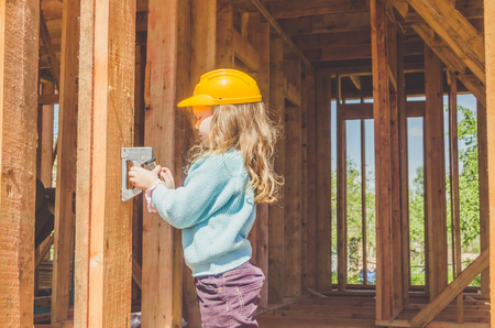 child, girl in a helmet on the construction site of a wooden frame house with a stapler in his hands 版權商用圖片