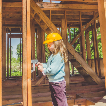 child, girl in a helmet on the construction site of a wooden frame house with a stapler in his hands 写真素材