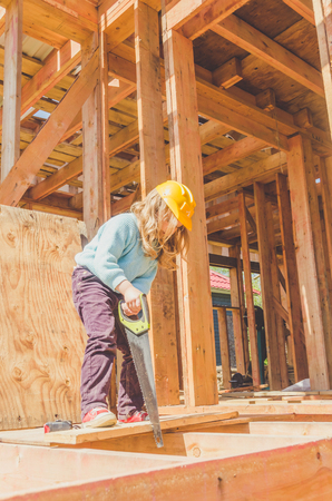 a child, a girl in a helmet on a construction site of a wooden frame house with a saw with a hacksaw in her hands Stock Photo