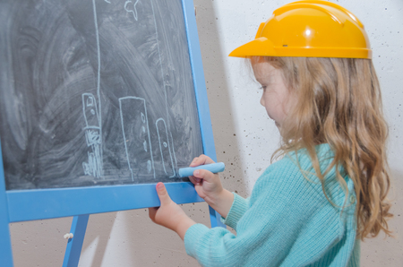 child engineer, designer, girl in a helmet paint a house on a black chalk Board