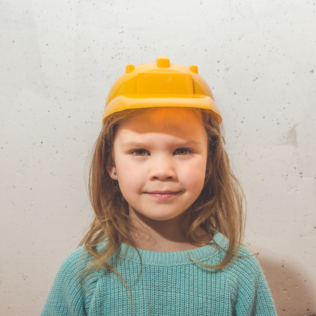 child at home at the white wall, a girl in a yellow construction helmet