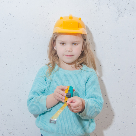 child worker, Builder, girl in a helmet measures the distance with a tape measure