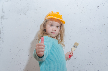 child worker, Builder, girl in a helmet paints the wall
