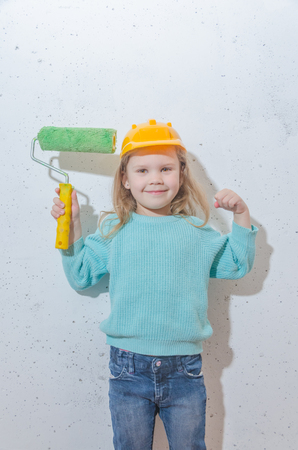 child worker, Builder, girl in a helmet paints the wall Stock Photo - 103256786