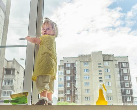 meisje, een kind op de vensterbank wast het raam op een zonnige dag