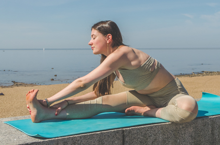 girl doing yoga, doing asanas in the Park, on the beach near the water