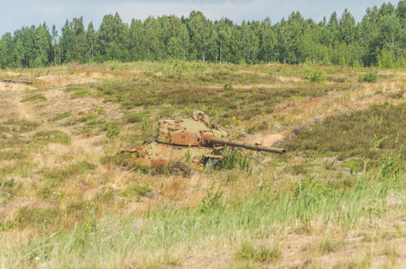 lined with rusty military tank, artillery, tracked, in the field on a Sunny day