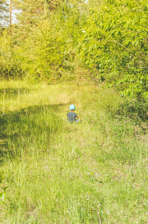 summer boy, child sitting in the forest on the meadow back