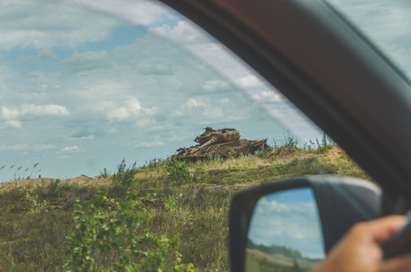 behind the wheel of the car you can see the battlefield with the destroyed rusty tank Stock fotó
