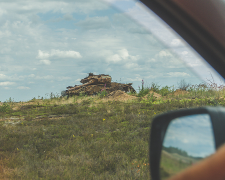 behind the wheel of the car you can see the battlefield with the destroyed rusty tank 版權商用圖片