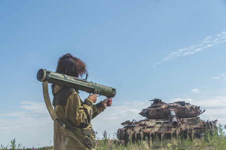 Sunny day girl in uniform with a Bazooka on the background of a broken tank on the battlefield Imagens