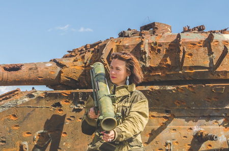Sunny day girl in uniform with a Bazooka on the background of a broken tank on the battlefield Stock fotó - 104124434
