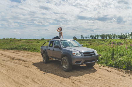 beautiful girl on an SUV in a field on a sandy road on a summer day Stock Photo - 104124521