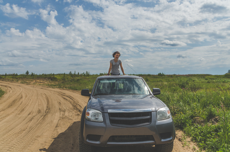 beautiful girl on an SUV in a field on a sandy road on a summer day