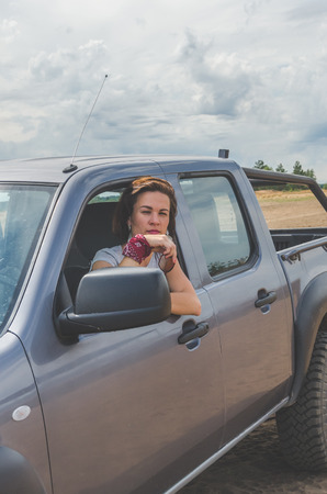 beautiful girl on an SUV in a field on a sandy road on a summer day Stock Photo - 104124572