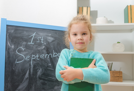 the girl, a student on the chalk Board the first of September, with a book