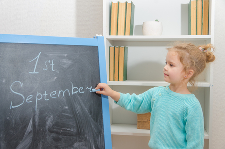 girl student writes on chalk Board the first of September Stock Photo