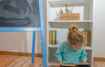girl, a child reading a book sitting at the chalk Board