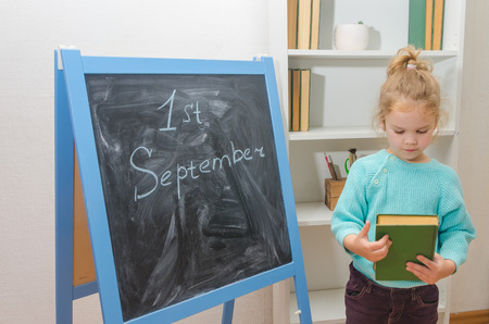 girl, a child at the chalk Board with the inscription on September 1 and a book in his hands