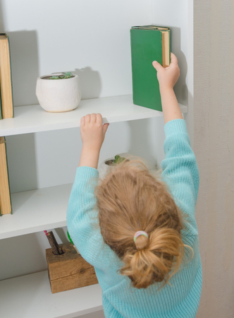 girl, the child puts the book on the shelf