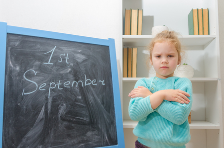 girl, a schoolboy on the chalkboard first of September, upset does not want to go to school