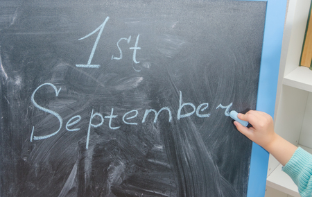 girl student writes on chalk Board the first of September Stok Fotoğraf