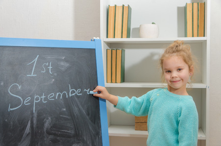 girl student writes on chalk Board the first of September Stok Fotoğraf - 104568867
