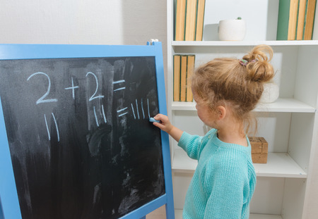 girl, a schoolboy on a chalkboard solves mathematical examples Stock Photo - 104568869