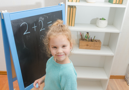 girl, a schoolboy on a chalkboard solves mathematical examples