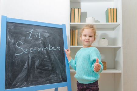 girl, child at the chalk Board with the inscription on September 1 and shows the sign of the class, excellent