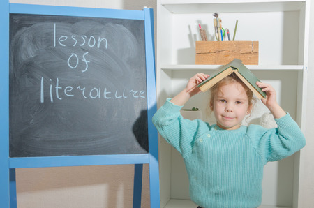 girl, a child with a book near the chalk Board with the inscription literature lesson Stock Photo