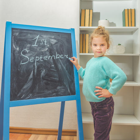a girl, a child, a Junior school student writes in chalk on the Board, the first of September Stok Fotoğraf - 104590943