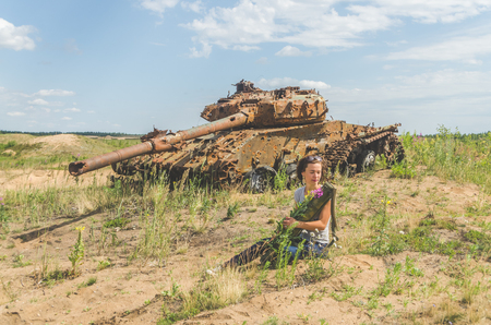 beautiful girl with flowers in her hands on the background of a rusty destroyed tank on the battlefield Stock fotó