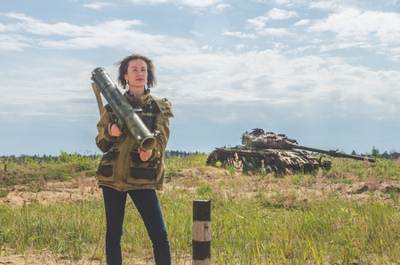 beautiful girl in military uniform and jeans with a Bazooka in her hands on the background of a rusty destroyed tank on the battlefield