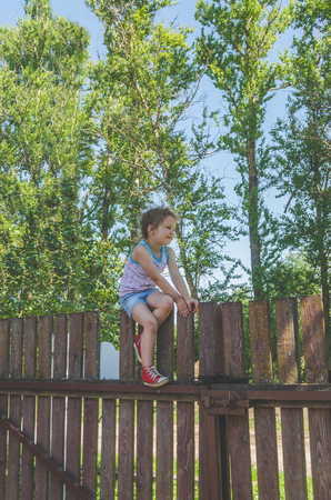 a child, a girl climbs a wooden fence in the village