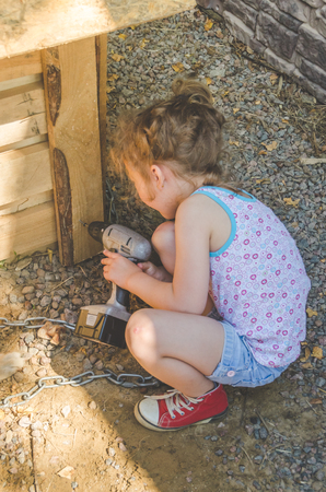 girl, child builds, repairs booth, house for dog Фото со стока
