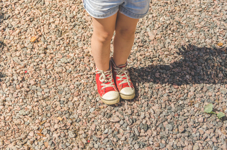 girl, child standing on stones, legs close-up