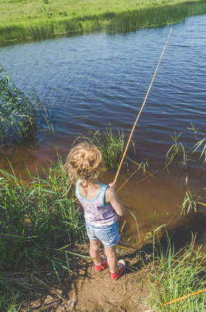 girl, child on a summer day fishing with a fishing rod and a net Imagens