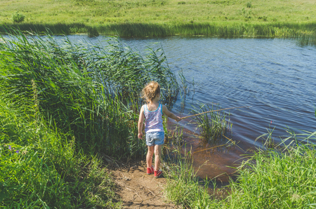 girl, child on a summer day fishing with a fishing rod and a net Standard-Bild