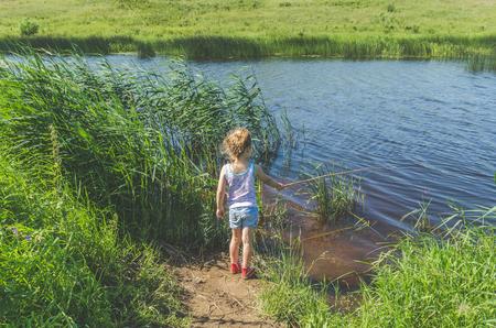 Mädchen, Kind an einem Sommertag Angeln mit einer Angelrute und einem Netz Standard-Bild - 105414317