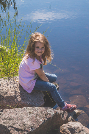 little girl sitting on a rock near the water
