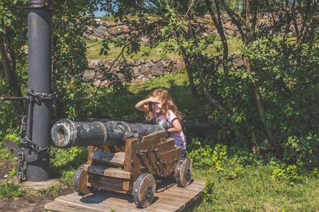 little girl playing with artillery gun