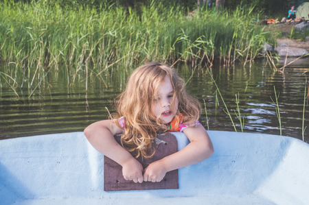 girl, a child in a life jacket fell out of the boat, holding the edge Stockfoto - 106212037