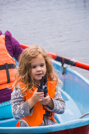 girl in a life jacket, a child in a boat, says on the radio