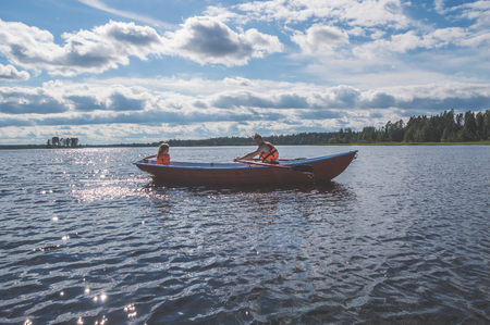 the man and the child, the girl in the boat, rowing on the lake Stock Photo - 106394310